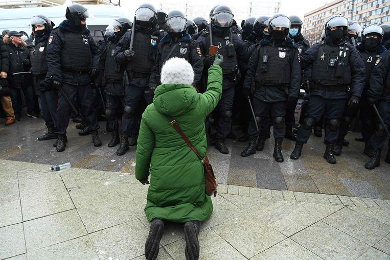 Een vrouw staat in een buitenwijk van Moskou tegenover een peloton van de oproerpolitie. Beeld AFP
