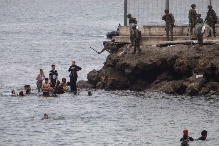 Jonge mannen, vrouwen met kinderen en hele families zwommen of voeren met opblaasbare bootjes naar Ceuta. Beeld AP