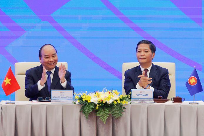 De Vietnamese premier Nguyen Xuan Phuc (L) en minister van Handel en Industrie Tuan Anh (R) tijdens de virtuele ondertekeningsceremonie van de handelsovereenkomst in Hanoi.