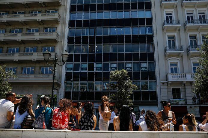 Personeel van een kantoor in Athene staan voor het ontruimde gebouw.