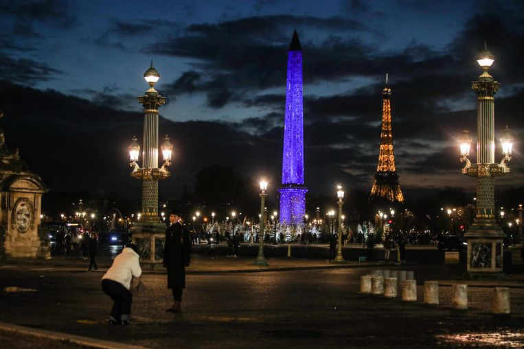 Toeristen maken een foto van een verlichte Eiffeltoren in Parijs. Beeld EPA