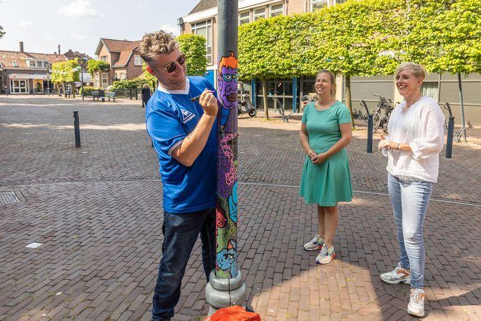 Kunstenaar Pieter Zandvliet geeft de lantaarnpaal op hoek Bloemendalstraat-Wilhelminastraat-Kerkplein in Dalfsen een kleurtje. De oude palen worden gepimpt. Ondernemers en initiatiefnemers Willeke Lindenburg (links) en Barbara van Nieuwenhuizen kijken toe.