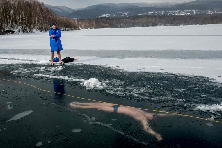 Het is nog maar een training, in het Barborameer in Tsjechië. Uiteindelijk gaat Deze Tsjech het nationaal record onder-het-ijs-zwemmen proberen te verbeteren. Dat staat momenteel op 76,2 meter. Het doel is 80 meter. Dat vergt een duik, zonder zuurstof, van 1 minuut en 40 seconden.  Beeld AFP