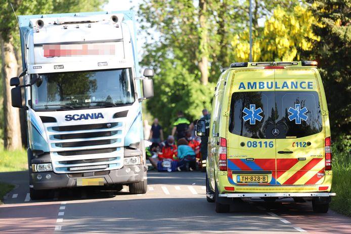 Medisch personeel verleent eerste hulp aan de brommerrijder, die in aanrijding is gekomen met de vrachtwagen.