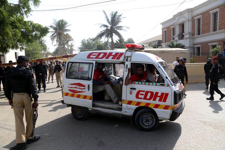 Een ambulance neemt een slachtoffer mee van de aanslag op het Chinese consulaat in miljoenenstad Karachi. Beeld EPA