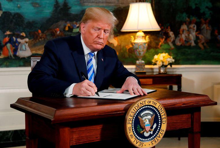 President Donald Trump ondertekent de verklaring om de VS terug te trekken uit het atoomakkoord met Iran. Beeld Reuters