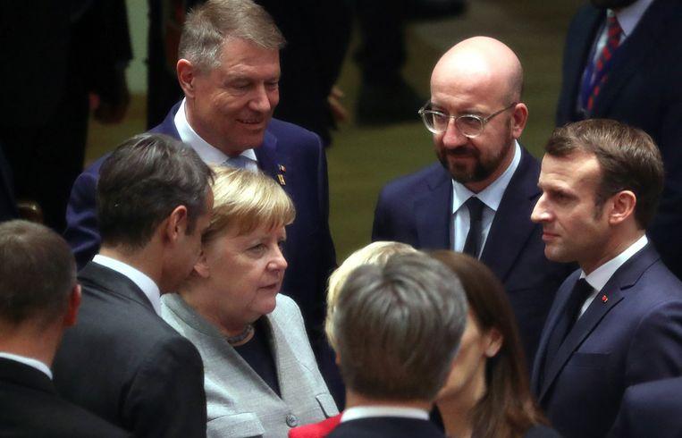 De Duitse kanselier Angela Merkel praat met de Franse president Emmanuel Macron en de voorzitter van de Europese Raad, Charles Michel. Merkel en Macron probeerden vergeefs hun gewicht in de schaal te gooien en Michel bij te springen, maar zij kwamen te laat. Beeld AP
