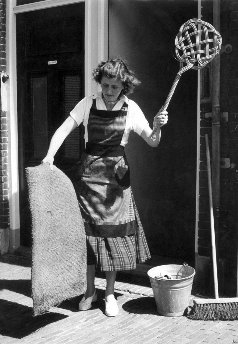 Matten kloppen. Hollandse huisvrouw met schort klopt de mat met een mattenklopper, op straat bij de voordeur. Naast haar een bezem en zinken emmer met dweil. 1955 of eerder.  Beeld Hollandse Hoogte / Spaarnestad Photo