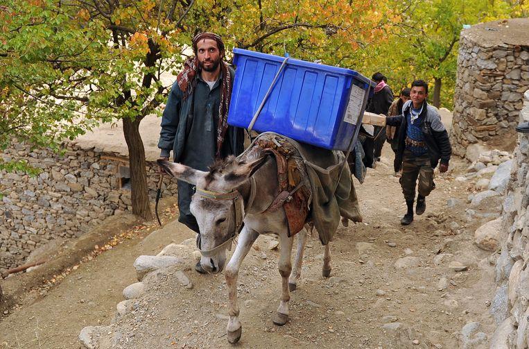 Afghaanse verkiezingsmedewerkers brengen stembussen en stemmateriaal naar de Abdullah Khil vallei in de noordelijke provincie Panjsher in Afghanistan. Beeld EPA