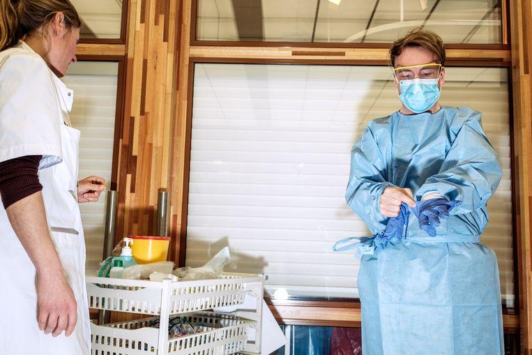 Een arts van het AMC kleedt zich aan voordat hij een mogelijke coronapatiënt behandelt. Beeld Jakob van Vliet