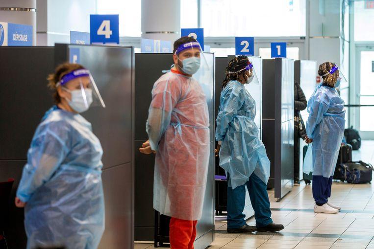 Mederwerkers van de teststraat op het vliegveld van Toronto  Beeld Reuters