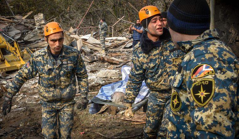 Reddingswerkers dragen het lichaam van een omgekomen vrouw weg. Beeld AFP