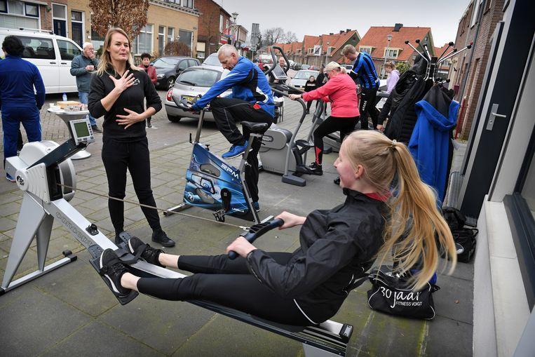 Roeien op de stoep bij sportschool Fitness Voigt in Tiel. Beeld Marcel van den Bergh / de Volkskrant