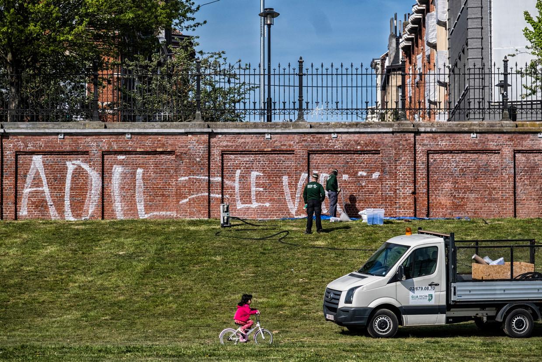 Op verschillende plekken in Brussel werden de steunbeteugingen aan Adil, zoals deze 'Adil = Le virus c'est la police' aan het park rond Tour & Taxis, al snel weer weggepoetst. Beeld Tim Dirven