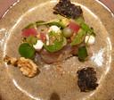 Dungesneden, in laagjes opgebouwde ceviche van gepekelde Corvina (baarsachtige vis) is afgedekt met oesters, zoetzure komkommerballetjes, avocado, tipjes mierikswortelcrème en cress.