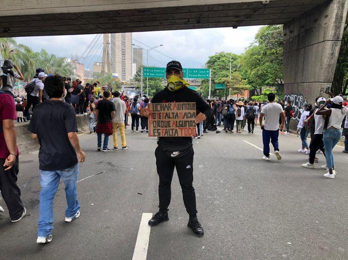 Yino Diaz tijdens het protest in Medellín. Op het bord: 'Ook al kom je zelf niks te kort, vecht voor degenen die alles te kort komen'