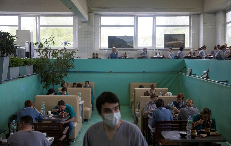Lunchtijd in de kantine (voorheen het zwembad) van stadskliniek nummer 15 in Moskou, waar Covid-19-patiënten worden behandeld. Beeld Reuters