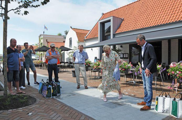 Wethouder Jacqueline van Burg heeft samen met aannemer René Moerland (r) op het Kerkplein een plaquette onthuld als afsluiting van deze fase van de herinrichting van het centrum van Bruinisse.