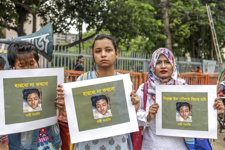 Vrouwen houden een foto vast van het negentienjarige meisje Nusrat Jahan Rafi. Zij werd levend verbrand nadat ze een klacht tegen het hoofd van een koranschool had ingediend voor seksuele aanranding.