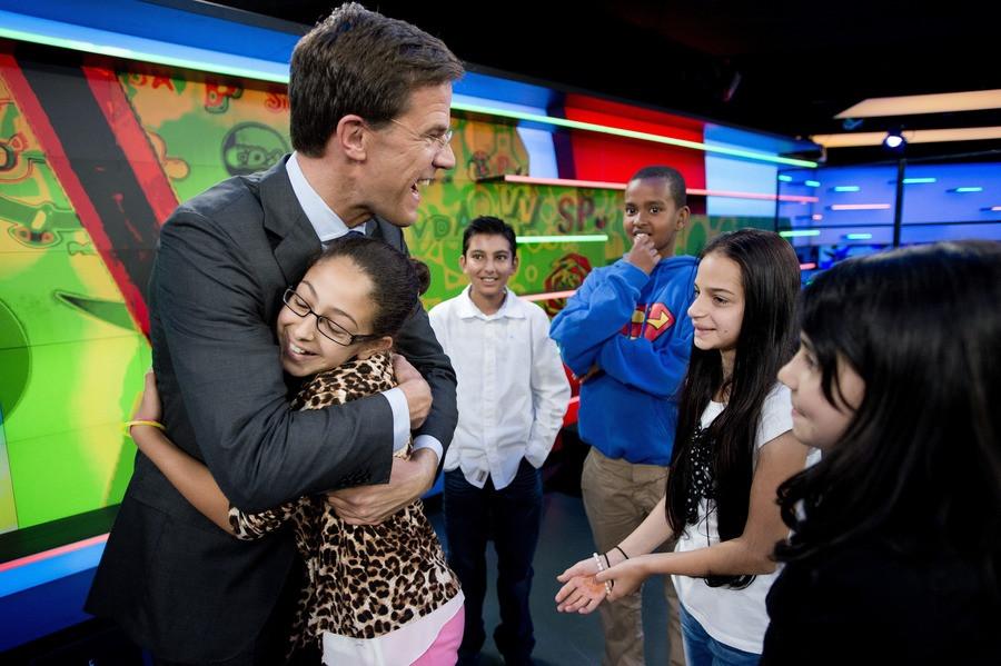 Lijsttrekker Mark Rutte krijgt een knuffel van een kind bij de opname van het Jeugdjournaal.