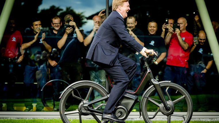Koning Willem-Alexander vermaakt zich op een futuristische elektrische fiets bij de opening van een nieuwe fabriek van Gazelle. Beeld EPA