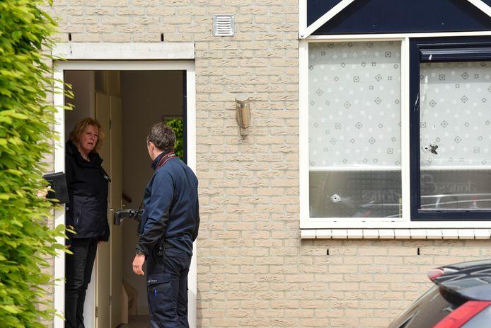 Medewerkers van de politie doen onderzoek in en om het huis na de beschieting.