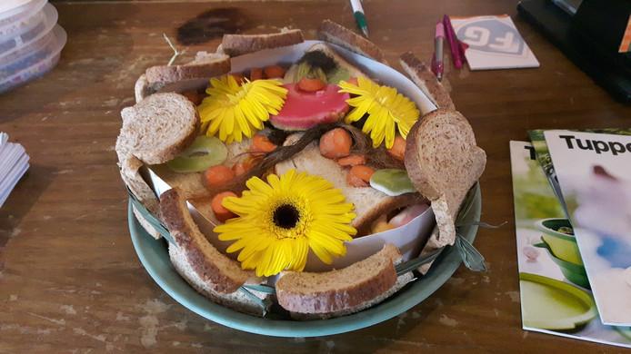 Een feesttaart met brood, ananas, bloemetjes, groenten en (snoep)spekjes.