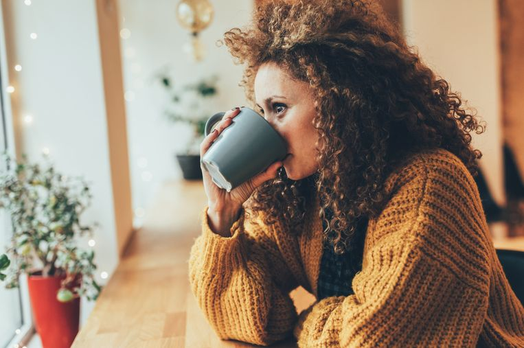 Attractive woman drinking coffee at the cafe. Beeld Getty Images
