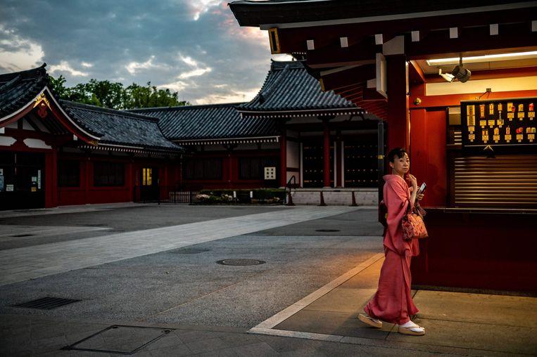 Een vrouw bij de Sensoji tempel in Tokio tijdens de eerste dag van de nieuwe noodtoestand. Beeld AFP