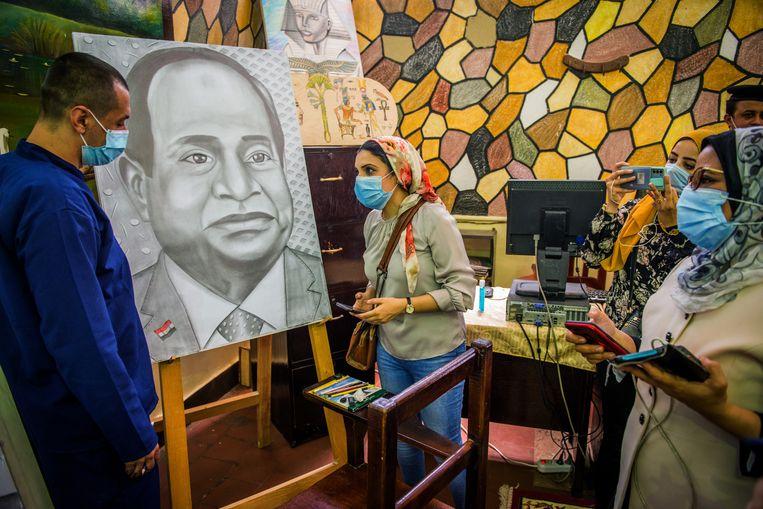 Op de recreatie- en knutselafdeling van de gevangenis werkt een gevangene aan een potloodtekening van president Sisi.   Beeld Rene Clement