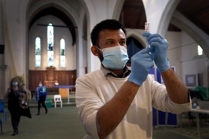 Een apotheker prepareert een spuitje met het coronavaccin in de St John's Church in Londen.
