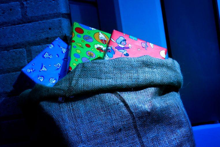 Een zak vol met sinterklaascadeautjes voor een huisdeur. Beeld ANP