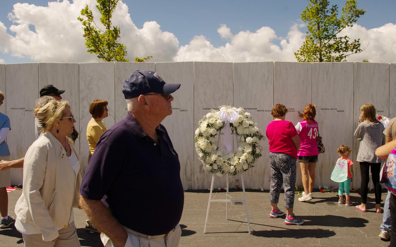 Bezoekers lopen voorbij een marmeren muur met de namen van de slachtoffers van United 93. Beeld Getty Images
