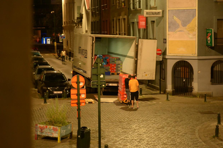 De vrachtwagen – tegen de richting in de straat ingereden – wordt gelost. Het geratel van de pallettrucks op kasseien maakt de buren stapelgek.  Beeld RV