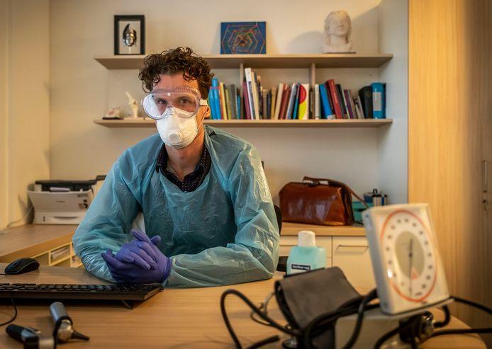 Huisarts Christian de Groot in zijn spreekkamer in Son in de beschermende kleding die hij vanwege het corona virus draagt tijdens contact met patiënten.