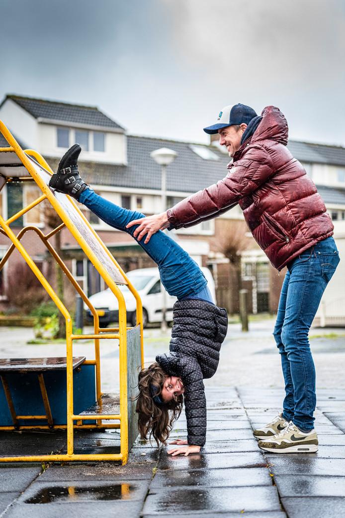 Vader en dochter Jimmy en Victoria van Delft in het speeltuintje voor hun huis