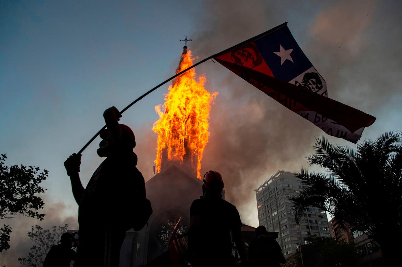 Een demonstrant zwaait met een Chileense vlag voor een brandende kerk in hoofdstad Santiago de Chile tijdens een demonstratie in oktober 2020 voor een 'nieuw Chili'.  Beeld AFP