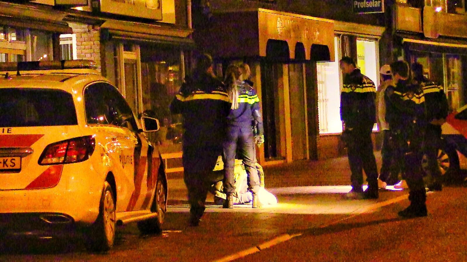 De verdachten zitten geboeid op het trottoir langs de Haaksbergerstraat.