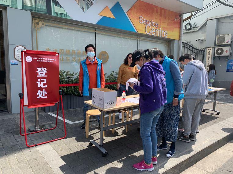 In de Penglaistraat in Sjanghai spreken vrijwilligers voorbijgangers aan. Ben je al gevaccineerd? Hier kan het meteen!  Beeld Eefje Rammeloo