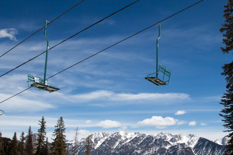 Two old two person ski lift chairs run on cables overhead.  The sky is blue with whisps of clouds.  Under the old chairs are snowcapped peaks of a mountain range.  The chair lift is painted green and both chairs are going opposite directions. Beeld thinkstock