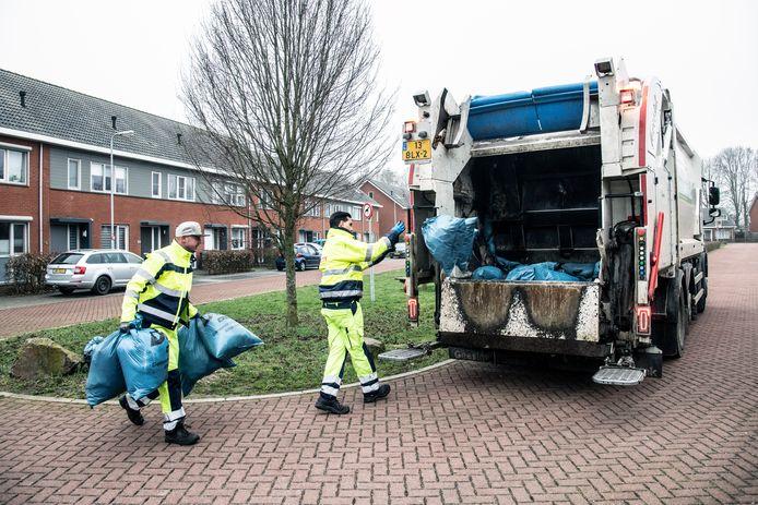 Ophalers gooien blauwe zakken de afvalwagen in in Millingen. Vanaf volgend jaar zal dit beeld in de straten van de gemeente Berg en Dal nog maar eens per maand te zien zijn. Nu wordt restafval nog om de twee weken opgehaald.