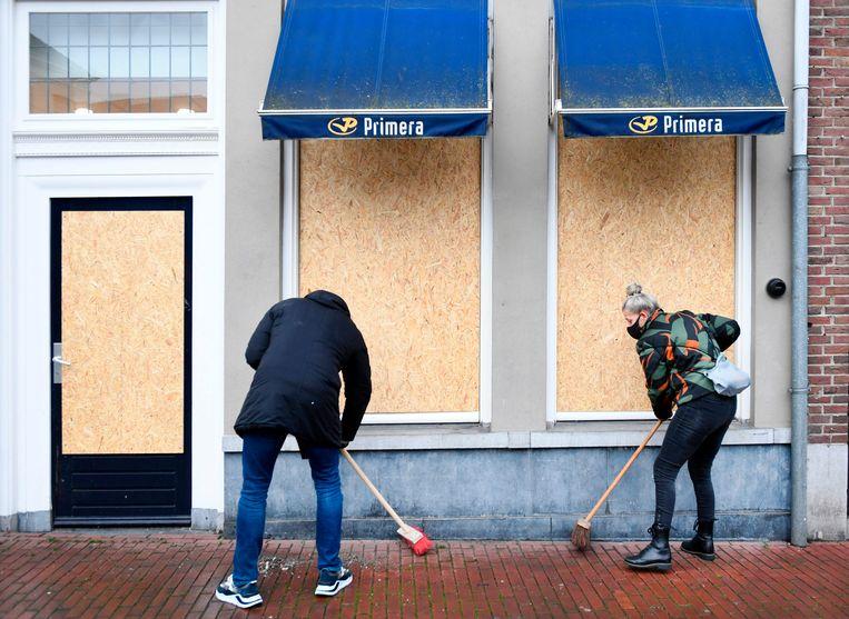 In afwachting van nieuwe ruiten zijn de ramen van de krantenwinkel vervangen door houten platen. Beeld AFP