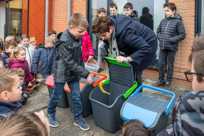 De Hulster wethouder Diana van Damme overhandigde verschillende afvalbakken om beter afval te scheiden op basisschool De Schakel in Vogelwaarde.