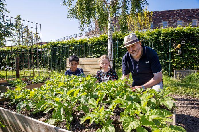 Knute, Lana en Frans van den broek in de moestuin van de vuurvlinder. De beide kinderen krijgen uitleg over de aardappelplanten.