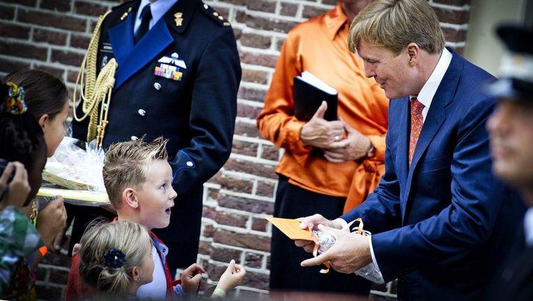 Koning Willem Alexander krijgt een brief overhandigd van een jongetje voorafgaand aan de uitreiking van het eerste exemplaar van het Droomboek op Paleis Het Loo Beeld anp