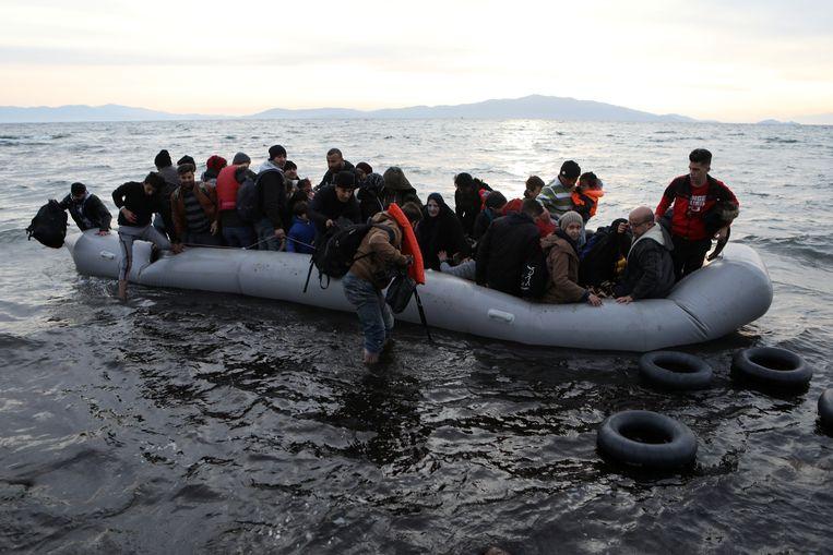 Ruim een jaar geleden arriveerden deze migranten uit Syrië, Irak en Afghanistan in een wankele rubberboot op Lesbos, na de zee tussen Turkije en Griekenland te zijn overgestoken. De mensen op de foto komen niet voor in dit verhaal.  Beeld Reuters