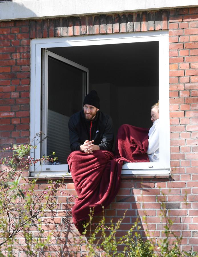 Een stel in Hamburg dat het advies opvolgt om thuis te blijven, geniet van de zon in het open raam van hun woning.