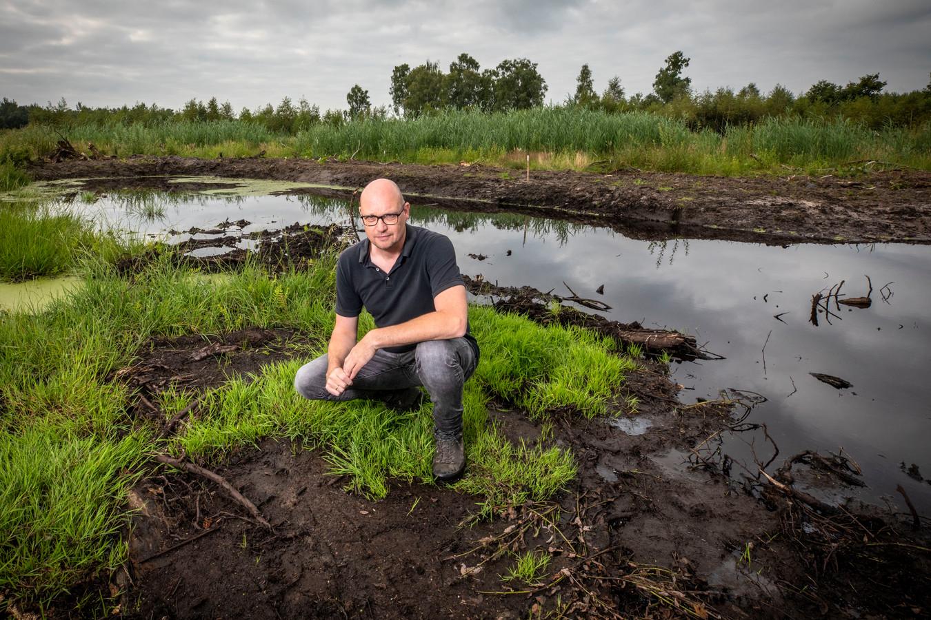 """Iwan Brinkhuis op de plek in het Aamsveen waar een illegale vuilstort is verwijderd. De poel is ongeveer 40 centimeter diep. """"Hier lag de rotzooi""""."""