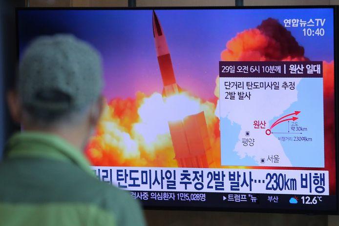Een Noord-Koreaan kijkt naar de raketlancering op nationale televisie.