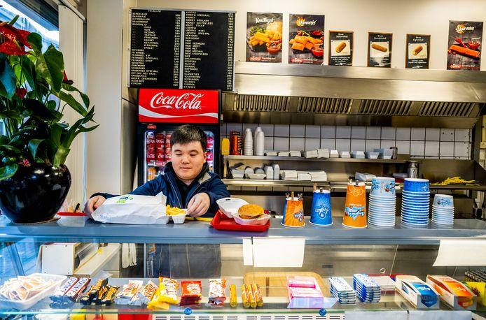 Snackbar Lin in Schiedam blijft vaak zitten met bestellingen, mensen bestellen telefonisch en komen het niet ophalen, vaak gaat het om grote bestellingen. Mensen bedenken van alles om er onderuit te komen. Zoon Winston op de foto. Foto: Frank de Roo